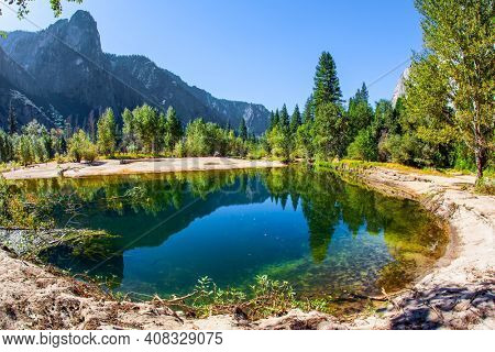 Yosemite Park is located on the slopes of the Sierra Nevada. Charming little lake in the Yosemite Valley. The El Capitan and trees is reflected in the smooth water