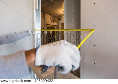Worker Measures Distance In Doorway After Instaliing Drywall In Apartment That Is Under Construction