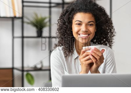 Smiling Young Cheerful African American Woman With Afro Hairstyle Enjoying Morning Coffee While Work