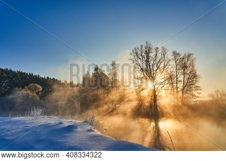 Winter Panorama With Trees Reflected In The Lake. Calm Winter Scene With Sunbeams And Warm Sunlight.