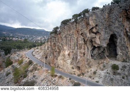 Road Under High Cliff In The Mountains. Aerial View Of Rocky Mountain Cliff Beside Highway Asphalt R