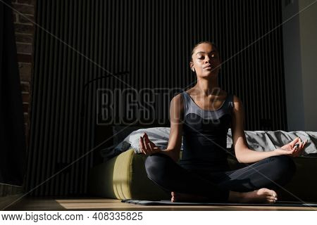 Attractive young healthy african woman doing yoga exercises on a fitness mat in the bedroom, yoga positions, meditate