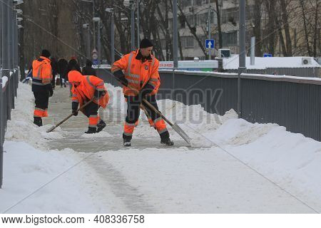 Kyiv Ukraine - February 10 2021: A Group Of Workers Remove Snow From A Sidewalk On A Footbridge Over