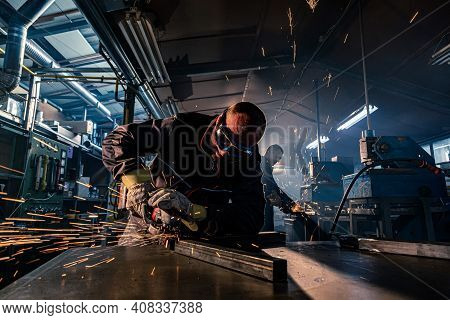 A Close-up Of Handyman Grinding In Workshop With A Colleague Grinding In The Background. He's Wearin