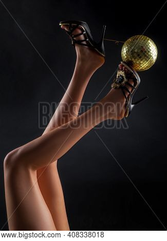 Holidays Event. Party Legs. Celebrating. Disco Ball On High Heels. Woman Heels With Gold Disco Ball.