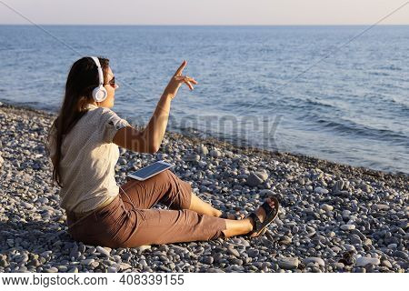 Young Woman In White Headphones Sits On Deserted Seashore Listening To Music And Singing Along To Th