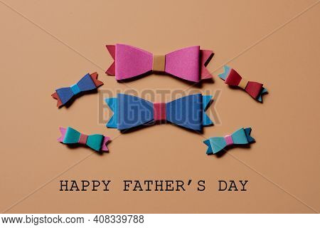 some symbolic bow ties of different colors and the text happy fathers day on a brown background