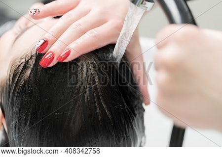 Hands Of Hairstylist Wash Long Hair Of Brunette Woman With Shampoo In Special Professional Sink For