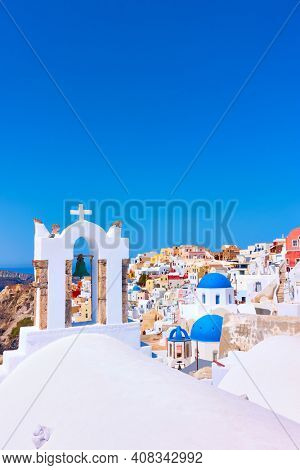 Greek landscape with old belfry in Oia town in Santorini island in Greece and large space for your own text over the blue sky on the top