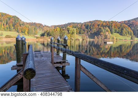 Interesting Brown Wooden Pier On The Shore Which Is Shaded, Public Bathing Place, Blue Lake In Autum