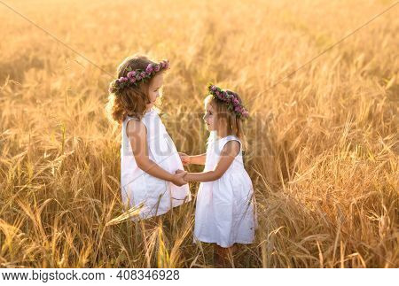 Two Girls With Wreaths Of Clover Hold Hands In A Field Of Wheat At Sunset. The Friendship Of Two Sis
