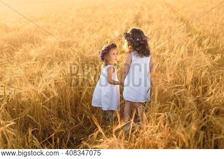 Two Girls With Wreaths Of Clover Play In A Field Of Wheat At Sunset. The Friendship Of Two Sisters.