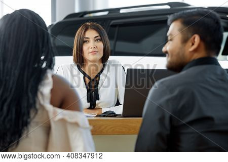 Visiting A Car Dealership. A Young African-american Couple To Communicate With The Agent For The Sal