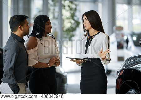 A Beautiful Couple Smiles While Looking At A New Car In A Car Dealership With A Seller. An Agent Dem