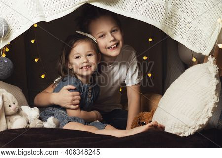 Siblings In A Hut Of Chairs And Blankets. Brother And Sister Laugh And Play At Home