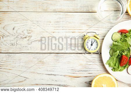Alarm Clock And Healthy Food On White Wooden Table, Flat Lay With Space For Text. Meal Timing Concep