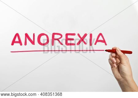 Woman Writing Word Anorexia On Glass Against White Background, Closeup