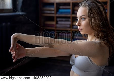 Young Pretty Woman In A Sport Suit Doing Stretching Exercises At Home. She Sits On A Yoga Mat And St