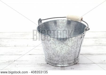 Empty Metal Bucket On White Grunge Wooden Table
