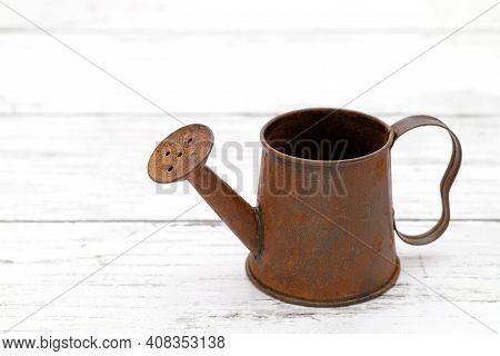 Rusted Old Miniature Watering Can On Wooden White Table