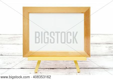 Natural Wooden Picture Frame On White Wooden Table