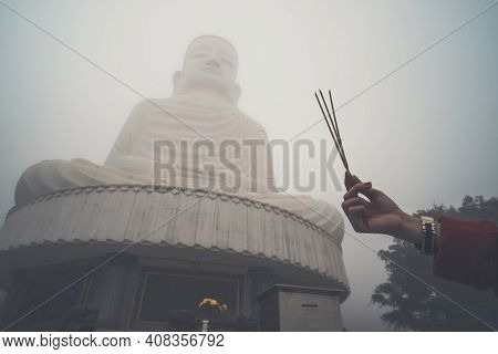 Buddha Image With Incense. Three Incense Sticks In A Woman's Hand Against A Big Buddha In The Fog. B