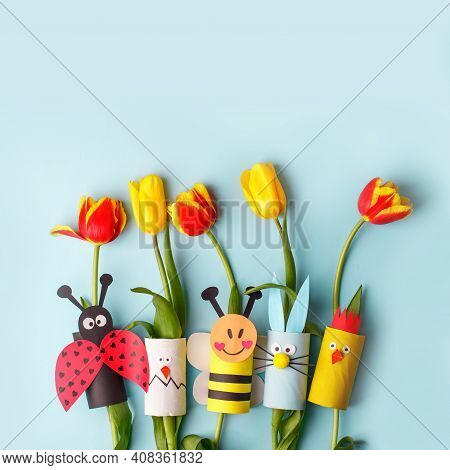 Happy Easter Spring Toy Collection And Fresh Flowers On Blue Background, Kids Holiday Party Concept