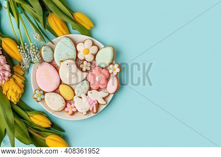 Easter Gingerbread With Icing On Plate, Seasonal Flowers On Blue, Festive Easter Background Web Bann