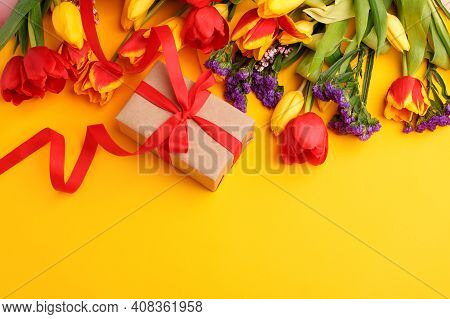 Colorful Tulips And Gift Box With Copy Space On Yellow. Background For Womens Day, 8 March Valentine