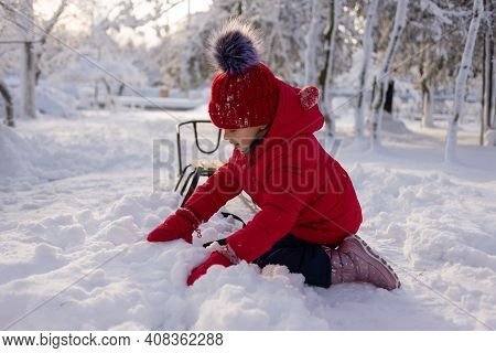 A Six-year-old Girl Sits On Her Knees In The Snow In A Winter Park With A Sleigh Nearby. The Child S