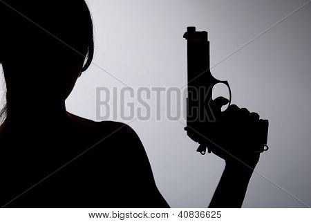 Silhouette Of A Woman With A Gun On A Gray Background