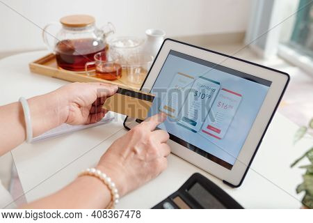 Hands Of Senior Woman Choosing Subscription Or Payment Plan On Tablet Computer And Paying With Credi