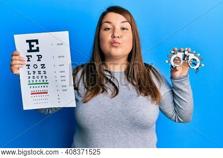 Beautiful brunette plus size woman holding optometry glasses and eyesight test looking at the camera blowing a kiss being lovely and sexy. love expression.