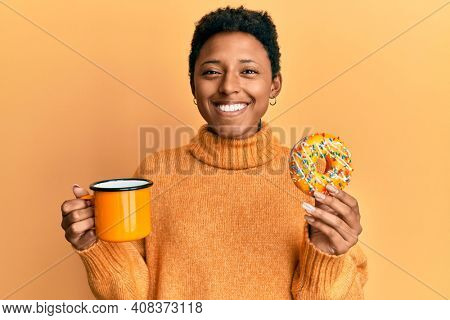 Young african american girl eating doughnut and drinking coffee smiling with a happy and cool smile on face. showing teeth.