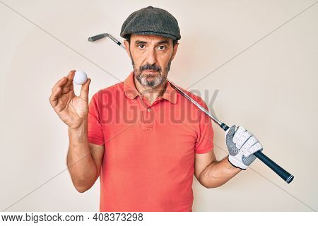 Middle age hispanic man holding golf club and ball relaxed with serious expression on face. simple and natural looking at the camera.