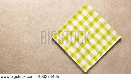 Folded checked or checkered tablecloth at stone surface of table. Top view of cloth napkin texture background
