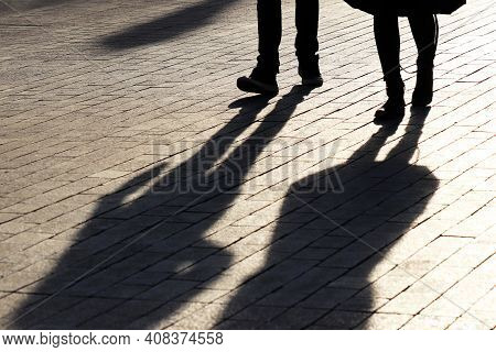 Silhouettes And Shadows Of Couple Walking Down The Street. Male And Female Legs, Concept Of Relation