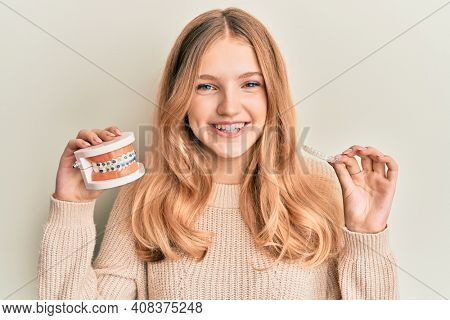Beautiful young caucasian girl holding invisible aligner orthodontic and braces smiling with a happy and cool smile on face. showing teeth.