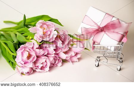 Close Up Of A Bunch Of Tulips Near A Small Shopping Cart With A Gift In It. Women's Day, Mother's Da