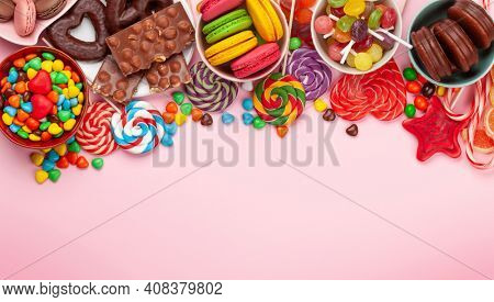 Various sweets assortment. Candy, bonbon, chocolate and macaroons over pink background. Top view flat lay with copy space