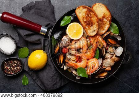 Mixed grilled seafood. Various roasted shrimps, mussels and shellfish in frying pan. Top view flat lay