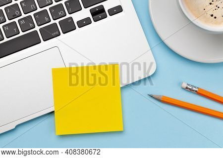 Office desk with yellow sticker, coffee and laptop. Remote office and work from home concept. Top view flat lay with copy space