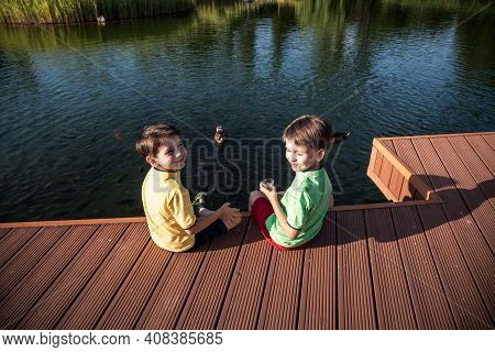 Two Children Feed The Wild Ducks And Shoal Of Small Fish In Azure Clean Transparent Lake. Brother Bo