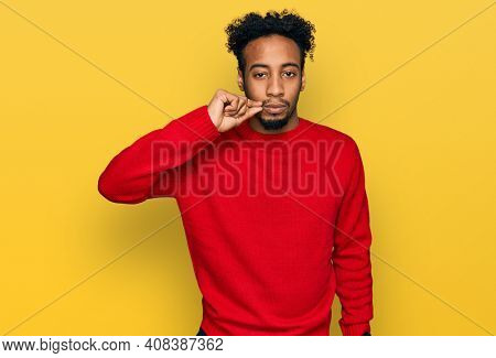Young african american man with beard wearing casual winter sweater mouth and lips shut as zip with fingers. secret and silent, taboo talking
