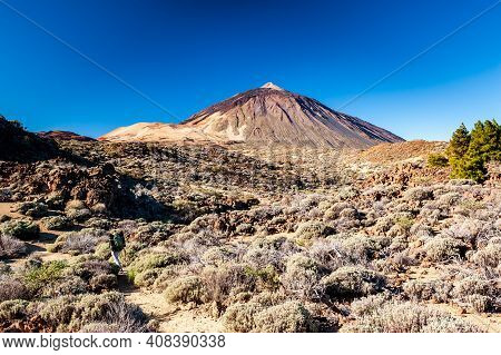 Silhouette Of Volcano Del Teide Against  Blue Sky And Female Hiker With Backpack. Pico Del Teide Mou