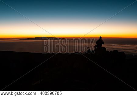 Tourist Man With Headlamp At Dawn Sitting And Waiting For Sunrise At Pico Del Teide Mountain In El T
