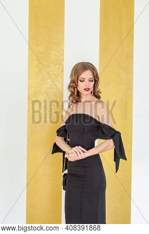 Glamorous Celebrity Model Woman In Black Cocktail Dress On Gold Background