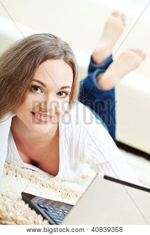 Frau arbeiten mit Laptop auf Teppich