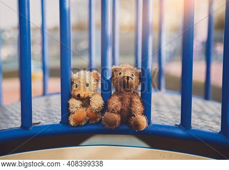 Two Lost Teddy Bear Lying On Metal Bridge At Playground In Gloomy Day, Lonely And Sad Face Brown Bea