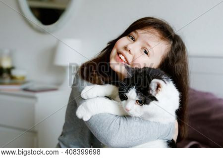 Cute Adorable School Kid Girl Cuddling And Playing Together With Cat In Bed In Morning. Happy Family